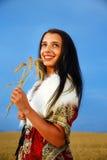 Giovane donna con il vestito ornamentale e la pelliccia bianca che stanno su un giacimento di grano con il tramonto Mazzo della t Immagini Stock