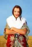 Giovane donna con il vestito ornamentale e la pelliccia bianca che stanno su un giacimento di grano con il tramonto Sfondo natura Immagini Stock