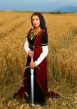 Giovane donna con il vestito ornamentale e la spada a disposizione che stanno su un giacimento di grano con il tramonto Sfondo na Immagine Stock Libera da Diritti