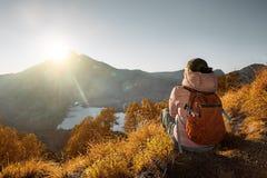 Giovane donna con il viaggiatore con zaino e sacco a pelo che gode della vista di alba all'alto mounta Fotografia Stock Libera da Diritti