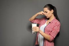 Giovane donna con l'allergia della latteria che tiene bicchiere di latte Immagini Stock Libere da Diritti