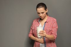 Giovane donna con l'allergia della latteria che tiene bicchiere di latte Fotografie Stock Libere da Diritti