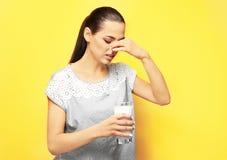 Giovane donna con l'allergia della latteria che tiene bicchiere di latte Fotografia Stock