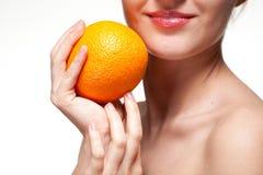 Giovane donna con l'arancia isolata su bianco Immagine Stock