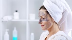 Giovane donna con l'asciugamano bianco sulla sua testa che spalma maschera cosmetica sul fronte stock footage