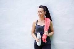 Giovane donna con l'asciugamano e la bottiglia di acqua dopo l'allenamento Fotografie Stock