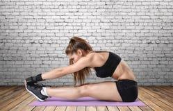 Giovane donna con l'ente atletico che fa allungando allenamento in vestito da addestramento, fuoco sulle mani Immagini Stock