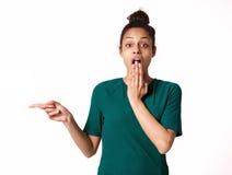 Giovane donna con l'espressione colpita che indica allo spazio della copia Fotografia Stock