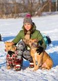 Giovane donna con l'inverno di Pit Bull Terrier di due americani Immagine Stock