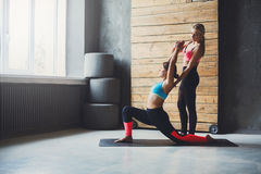 Giovane donna con l'istruttore di yoga nel club di forma fisica, posa del guerriero Fotografia Stock