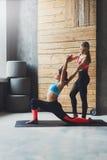 Giovane donna con l'istruttore di yoga nel club di forma fisica, posa del guerriero Fotografie Stock Libere da Diritti