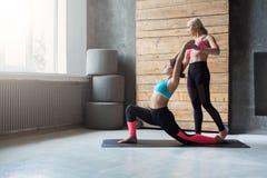 Giovane donna con l'istruttore di yoga nel club di forma fisica, posa del guerriero Immagine Stock
