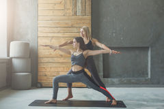 Giovane donna con l'istruttore di yoga nel club di forma fisica, posa del guerriero Immagini Stock