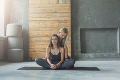 Giovane donna con l'istruttore di yoga nel club di forma fisica, posa del loto Immagini Stock