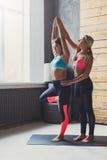 Giovane donna con l'istruttore di yoga nel club di forma fisica, posa dell'albero Immagine Stock Libera da Diritti