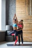Giovane donna con l'istruttore di yoga nel club di forma fisica, posa dell'albero Immagini Stock