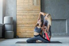 Giovane donna con l'istruttore di yoga nel club di forma fisica, posa della sirena Immagini Stock