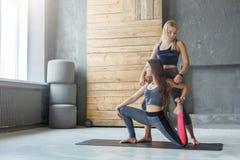 Giovane donna con l'istruttore di yoga nel club di forma fisica, posa della sirena Fotografia Stock