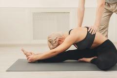 Giovane donna con l'istruttore di yoga nel club di forma fisica Immagine Stock Libera da Diritti