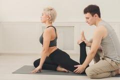 Giovane donna con l'istruttore di yoga nel club di forma fisica Fotografie Stock