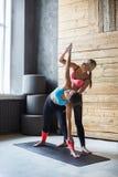 Giovane donna con l'istruttore di yoga nella classe di forma fisica, posa del triangolo Immagine Stock