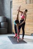 Giovane donna con l'istruttore di yoga nella classe di forma fisica, posa del triangolo Immagine Stock Libera da Diritti