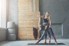 Giovane donna con l'istruttore di yoga nella classe di forma fisica, posa del triangolo Fotografia Stock