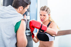 Giovane donna con l'istruttore in pugilato d'allenamento di pugilato Fotografie Stock Libere da Diritti