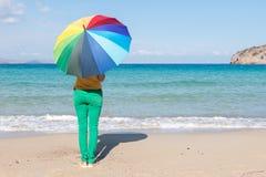 Giovane donna con l'ombrello variopinto sulla spiaggia Concetto di estate fotografia stock libera da diritti