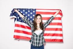 Giovane donna con la bandiera degli Stati Uniti in mani sulla parte posteriore di bianco Immagine Stock