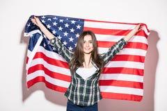 Giovane donna con la bandiera degli Stati Uniti in mani sulla parte posteriore di bianco Immagini Stock Libere da Diritti