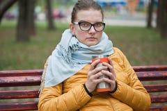 Giovane donna con la bevanda calda nel parco Fotografia Stock Libera da Diritti