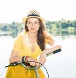 Giovane donna con la bici d'annata in una strada campestre vicino al lago O fotografia stock libera da diritti