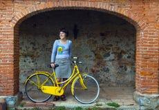 Giovane donna con la bici gialla fotografie stock