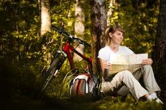 Giovane donna con la bicicletta in foresta Fotografia Stock Libera da Diritti