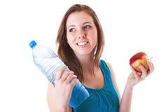 Giovane donna con la bottiglia di acqua e della mela Fotografie Stock