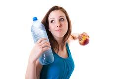Giovane donna con la bottiglia di acqua e della mela Immagine Stock Libera da Diritti