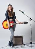 Giovane donna con la chitarra in sua mano Immagini Stock