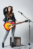Giovane donna con la chitarra in sua mano Immagine Stock