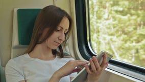 Giovane donna con la compressa che si siede sul treno stock footage