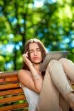 Giovane donna con la compressa digitale nel parco Fotografie Stock Libere da Diritti