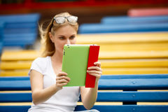 Giovane donna con la compressa in mani mentre sedendosi sul banco Fotografie Stock Libere da Diritti