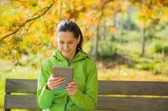 Giovane donna con la compressa nel parco di autunno Fotografia Stock