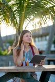 Giovane donna con la compressa sulla spiaggia fotografia stock