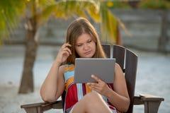 Giovane donna con la compressa sulla spiaggia immagine stock libera da diritti