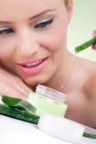 Giovane donna con la crema naturale di vera dell'aloe Immagini Stock
