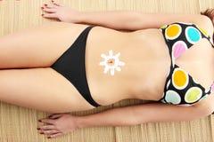 Giovane donna con la crema sole-a forma di del sole Immagini Stock Libere da Diritti