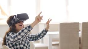 Giovane donna con la cuffia avricolare di realtà virtuale o i vetri 3d che si siede sul sofà a casa archivi video