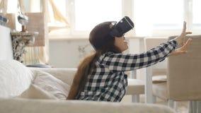 Giovane donna con la cuffia avricolare di realtà virtuale o i vetri 3d che si siede sul sofà a casa video d archivio