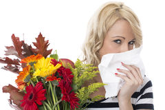 Giovane donna con la febbre da fieno che tiene un mazzo di fiori Immagine Stock